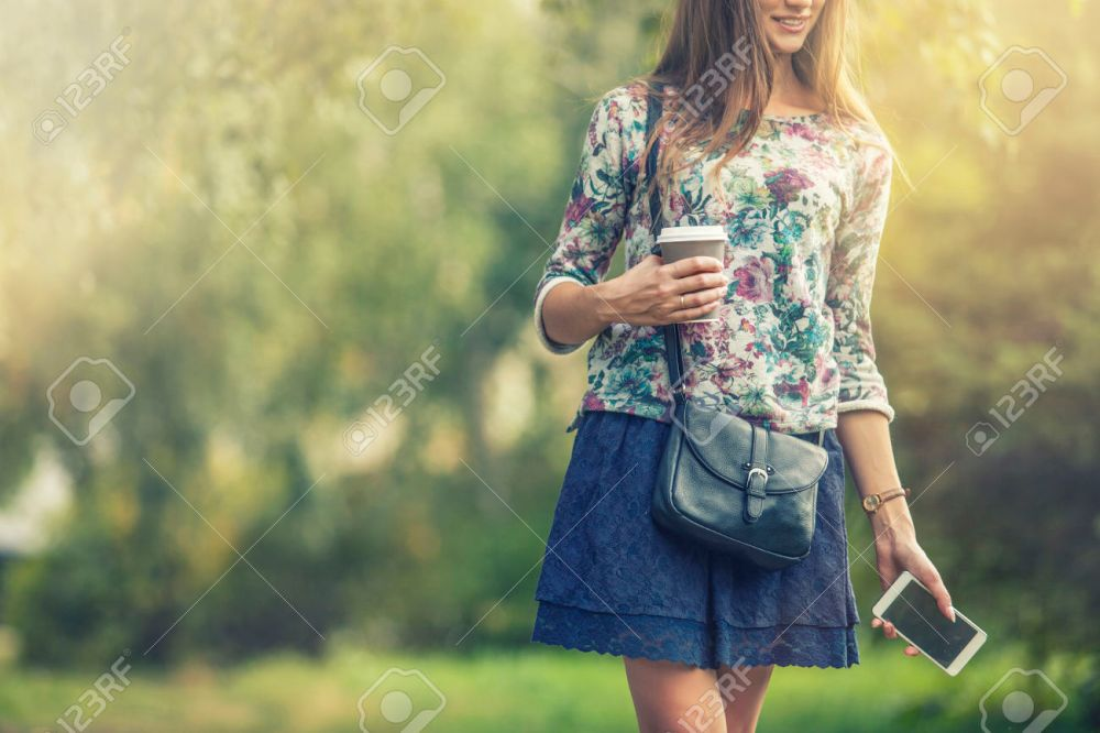 Beautiful woman model with take-away coffee and a telephone in t